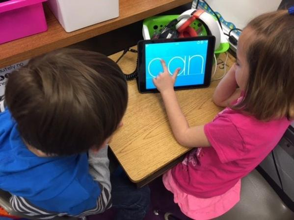 Photo of two children learning on an iPad