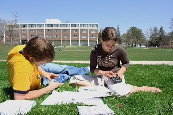 Two school students studying outside a school building