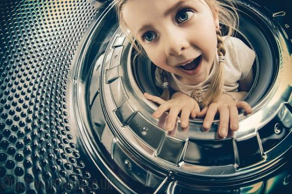 a 5 year old girl with her head in a washing machine
