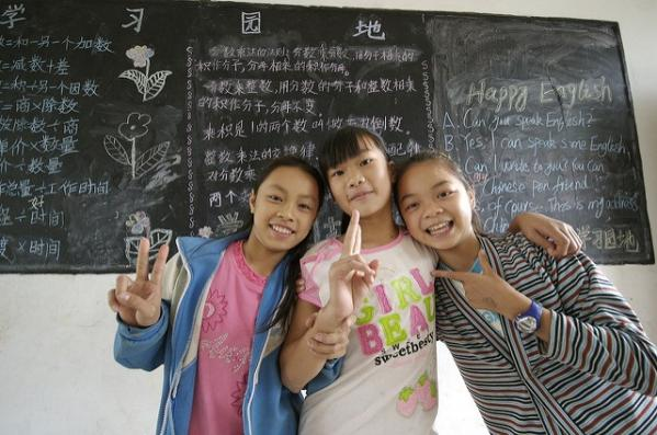 Three Chinese school students in front of a blackboard
