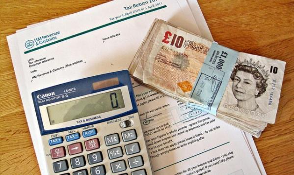 Photo of HMRC documents, money and a calculator